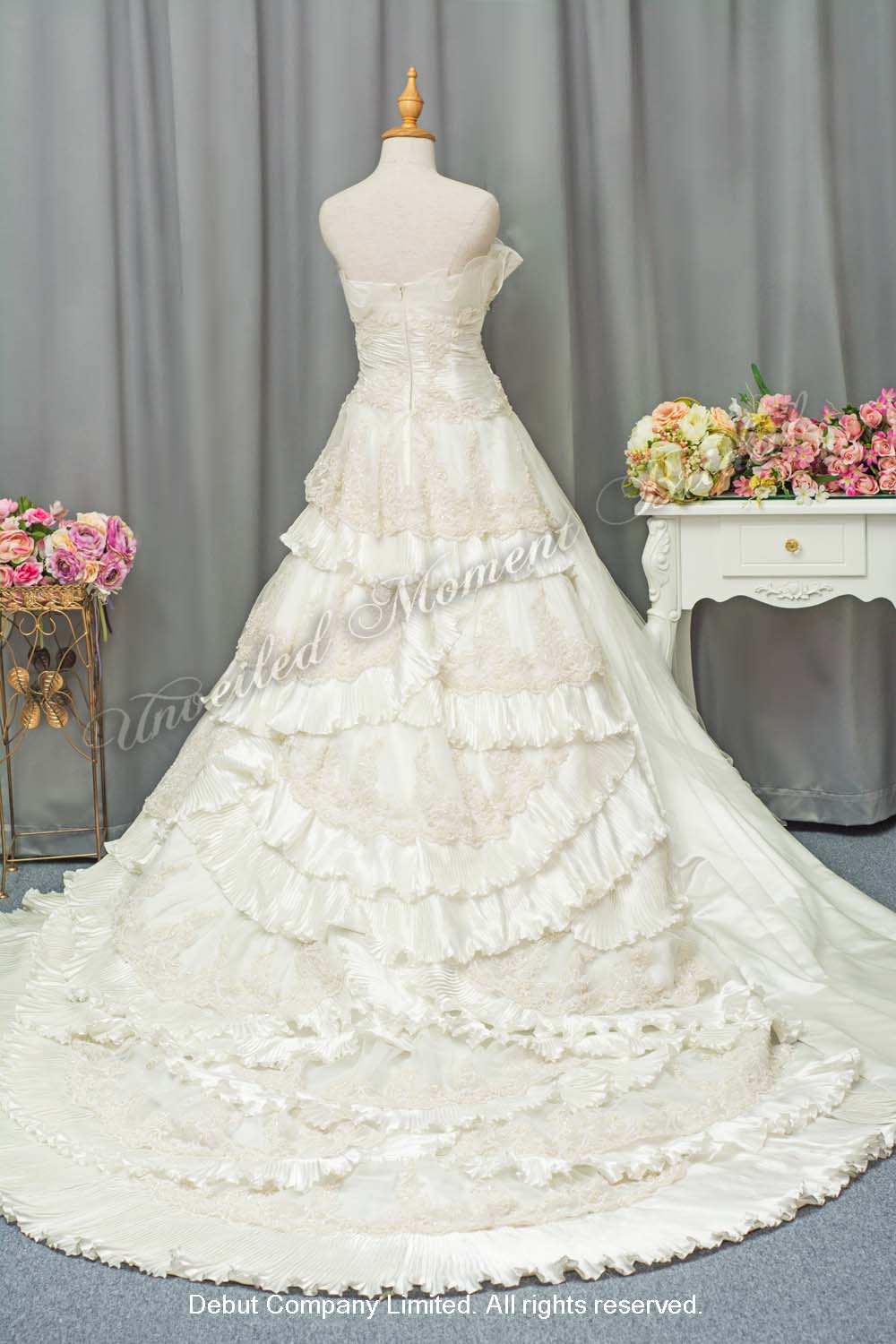 Strapless bridal dress with ruched bodice, chapel train, and asymmetrical layers of lace and pleated ruffles. 無肩帶, 褶疊設計上身, 不對稱層疊設計, 蕾絲釘珠, 長拖尾婚紗